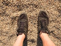 Legs in black sport shoes walking on sandy ground. Man hairy skin legs in black shoes Stock Photos