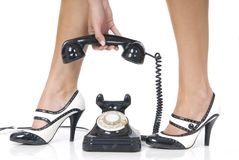 Legs with black and white shoes and telephone Stock Images