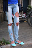 Legs in Blue Destroyed Jeans Stock Photo