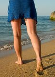 Legs in blue skirt going to the sea Stock Image
