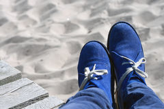 Legs in blue suede shoes on the sand Royalty Free Stock Images