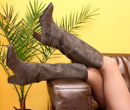 Legs in boots. Female legs in fashion boots on a sofa on a yellow background with green flower Stock Photos