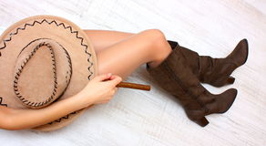 Legs, boots, hat and cigar. Sexy legs in fashion boots a cowboy hat and hand with cigar on a floor Stock Photography