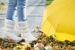 Legs in boots with umbrella. Autumn street closeup Royalty Free Stock Photo