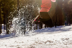 Legs bouncing girls, snow flies glistening in the sun. Legs girls Bouncing, flying snow glitters in the sun. Winter day Royalty Free Stock Photo