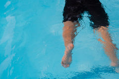 Legs of a boy drowning in the pool. A boy drowning in the pool, swimming cramps Royalty Free Stock Image