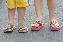 Legs of boy & girl. In slipper, on a tar road royalty free stock photos