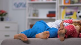 Legs of boy and girl lying on sofa, resting after active leisure, daytime sleep. Stock footage stock footage