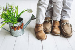Legs of boy and man, in moccasins with flowers. In watering can stock photos