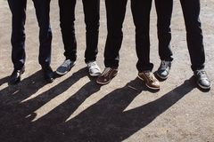 Legs of people with shadow. Legs of boys in sneakers with shadow Royalty Free Stock Photos