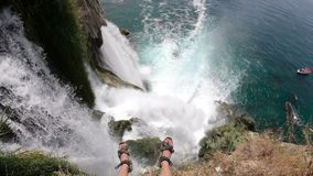 Legs of Brave Man Sitting on the Top of the Picturesque Lower Duden Waterfall Falling into the Sea in Antalya, Turkey. Legs of Brave Man Sitting on the Top View stock footage