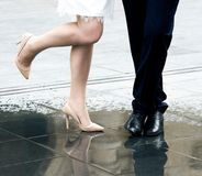 Legs of bride and groom on wedding day, black and white photo Stock Image