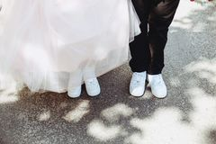 Legs of the bride on the pavement in sneakers and dresses royalty free stock images