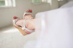 Legs of bride in wedding shoes. Bride in wedding dress sits on a bench with her legs showing wedding shoes Stock Photos