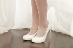 Legs of a bride in white shoes Stock Image