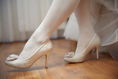 Legs of bride with white stockings and white shoes Stock Photo