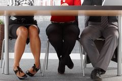Legs of businesspeople at meeting. Sitting together at meeting table in office stock images