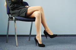 Legs of businesswoman. Sitting on the office chair stock images