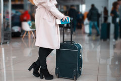 Legs of businesswoman with baggage in airport. Royalty Free Stock Images