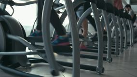 Legs in cardio machines. Doing workout. Shallow depth of field. Slow motion stock footage
