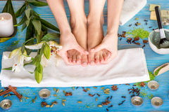 Legs care in spa. Woman taking care of her legs on the bath towel in spa with flower, candles and herbs on blue wooden desk Royalty Free Stock Image