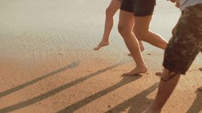 Legs of Caucasian family walking barefoot on beach and waves stock video