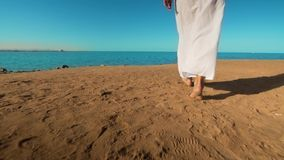 Legs of caucasian girl wearing white long dress walking barefoot sand on sea beach stock footage