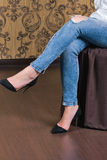 Legs of Caucasian woman sitting wearing torn jeans. Royalty Free Stock Photo