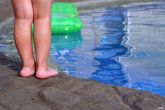 Legs of the child. The small child on coast of a swimming pool Royalty Free Stock Image