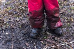 The legs of a child in dirty overalls and stained shoes, standing on the ground. stock image
