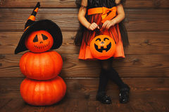 Legs of child girl in witch costume for Halloween with pumpkin royalty free stock photos