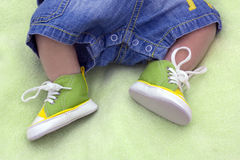 Legs of the child in gym shoes on a green blanket Royalty Free Stock Photos