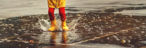 Legs of child with rubber boots jump in puddle on autumn walk Stock Photography