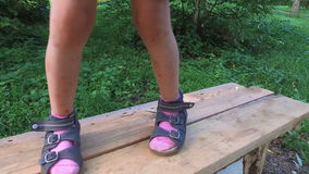 Legs of child  stepping on narrow wooden planks. Boards are located high above the ground. stock video footage