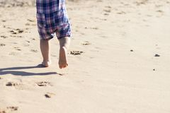 Legs of children stand on the beach. Baby feet in the sand. Summer beach background. Summertime holidays concept. Copy space Stock Photo