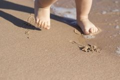 Legs of children stand on the beach. Baby feet in the sand. Summer beach background. Summertime holidays concept. Copy space. Stock Images