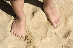 Legs of children stand on the beach with copy space royalty free stock photography