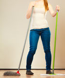 Legs of cleaning woman holds two mops new and old Royalty Free Stock Image