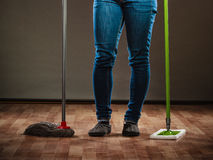 Legs of cleaning woman holds two mops new and old Royalty Free Stock Photography