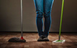 Legs of cleaning woman holds two mops new and old Royalty Free Stock Images