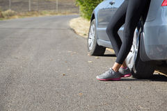 Legs close up near the car. Legs athletic woman standing near the car on the road Royalty Free Stock Photos
