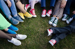 Legs in colored shoes. A lot of legs in multi-colored shoes, sneakers, sneakers Stock Image