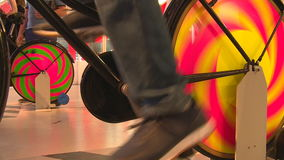 Legs on colorful static pedal bicycle generating electricity. Handheld closeup shot stock video