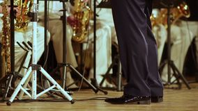 Legs conductor of brass band in black trousers and patent leather shoes. Close-up stock footage