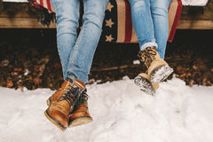 Legs of couple in boots on the wooden floor outdoors Royalty Free Stock Images