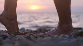 Legs of couple in love during the date near the sea on the beach during beautiful sunset. Man raising up on hand her loving woman stock photos