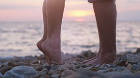 Legs of couple in love during the date near the sea on the beach during beautiful sunset. Man raising up on hand her loving woman Royalty Free Stock Image