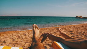 Legs of Couple People Lying on Beach Sun Lounger near the Red Sea stock footage