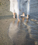 Legs of couple on the sand beach royalty free stock photography