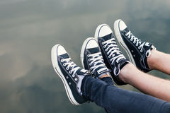 Legs of couple sitting above the water stock images